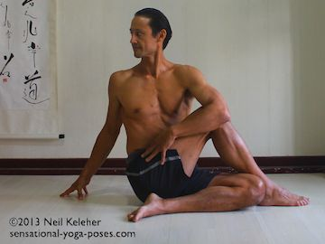 ardha matsyendrasana seated yoga pose. Step one leg over the other. Have foot just beside the other knee. In this picture the opposite arm is hugging the top knee. The other hand is on the floor behind the back. Both arms are being used to turn the ribcage and twist the spine. Neil Keleher. Sensational Yoga Poses.