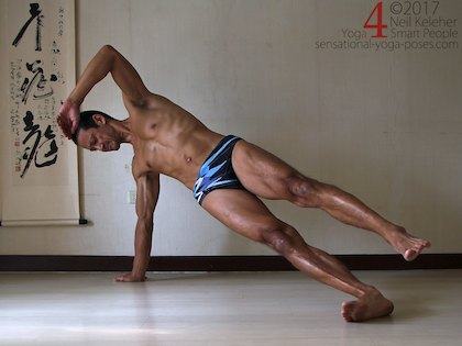 Balnacing in side plank with hips lifted and top foot lifted. Neil Keleher. Sensational Yoga Poses.