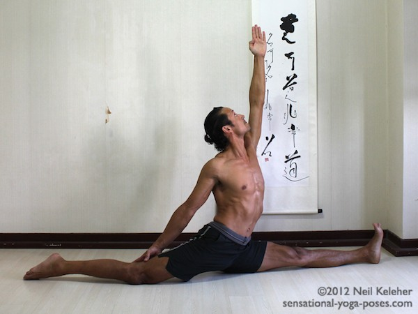 In this back bending front to back splits the upper body is upright. Both knees are straight with the back knee pointing down. The back leg arm is reaching towards the back knee. The front leg arm is reaching upwards.