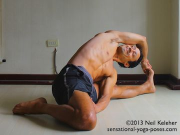 One option for a seated side bend is to sit with legs wide, with one knee straight and the other knee bent with the shin folded to the outside of the thigh (hero position). Bend towards the straight leg to stretch the side of the torso. In this case the top hand grabs the foot of the straight leg with the uppermost side of the ribcage rolling back. The lower shoulder is to the inside of the leg and pressing back against the leg.  Neil Keleher. Sensational Yoga Poses.