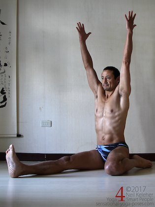 half hero yoga pose upright quad stretch, sitting with spine long and reaching arms upwards.