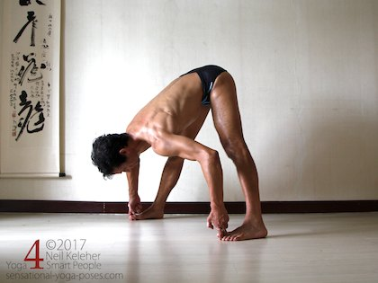 Wide leg standing forward bend, bending forwards at the hips with hands grabbing the big toes.  Neil Keleher. Sensational Yoga Poses.